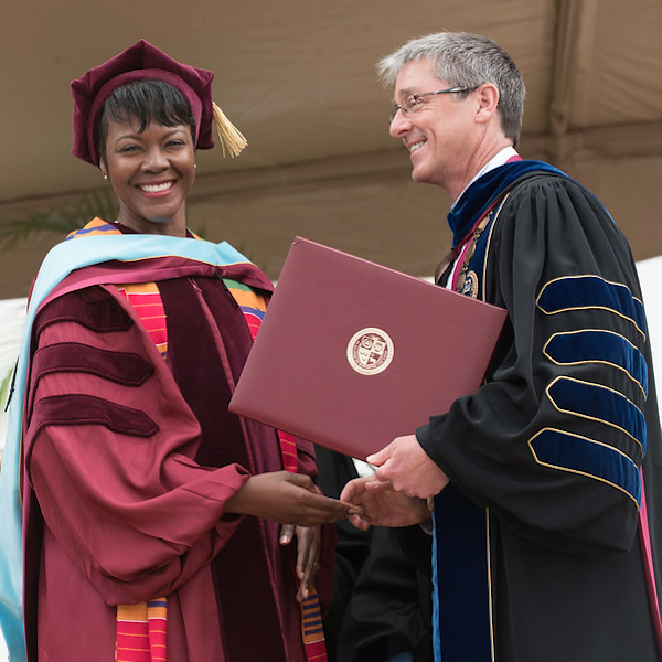African American woman accepts doctoral degree from President Snyder.