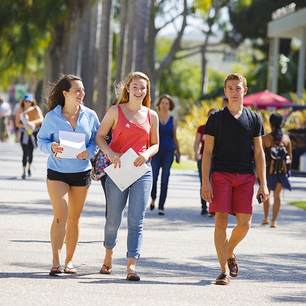 Two female and one male student walking together on campus.